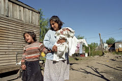 Poverty, mother and children in slum. ARGENTINA: blind, disabled girl with her mother and brother for their poor house in the village Pacheco Los Troncos, in the Royalty Free Stock Image
