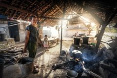 Poverty mother prepares and cooks meal for her child under basic shelter. INDONESIA, BALI, PENIDA ISLAND - AUGUST 2014: Unidentified mother prepares and cooks stock photos