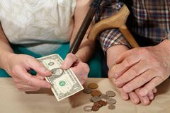 Poverty. Old couple and small coin. Stock Image