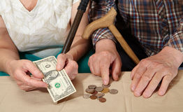 Poverty. Old couple and small coin. Royalty Free Stock Images
