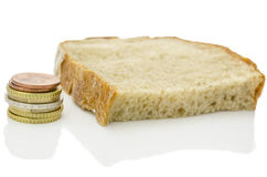 Poverty. Piece of bread and Euro coins over white background. Poverty concept royalty free stock photos