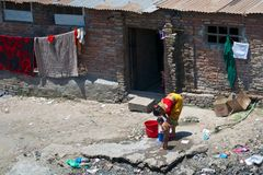 Poverty. Poor woman washes a child in the littered slums in the city Kathmandu, Nepal Stock Photos