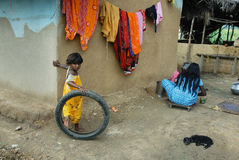 Poverty in Rural India. April 12, 2012.Purulia,West Bengal,India,Asia-A tribal girl playing with a car tyre in a remote village of West Bengal Royalty Free Stock Photo