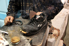 Poverty - Tunisia. A cobbler repairs an old pair of trainers (Reebook) in a street market (medina) in Kairouan - Tunisia. In Africa second hand items are fixed royalty free stock photo