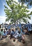 Povos africanos que protegem sob uma árvore no calor do sol imagens de stock royalty free