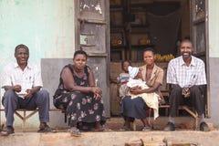 Povos africanos que sentam-se na frente da casa foto de stock