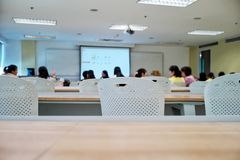 Povos aglomerados que atendem ao evento do seminário Cadeiras vazias na sala de aula com estudantes borrados dentro imagens de stock