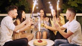 Povos alegres novos que sentam-se no café na noite com chuveirinhos do fogo de artifício video estoque