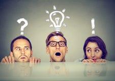 Povos ansiosos assustado dois homens e uma mulher que esconde espreitando o formulário sob a tabela que tem perguntas e ideias re Imagem de Stock Royalty Free