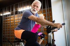 Povos aptos maduros que biking no gym, exercitando os p?s que fazem bicicletas de ciclagem do cardio- exerc?cio imagens de stock