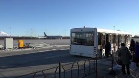 Povos aptos no aeroporto em um ônibus para o transporte aos aviões filme