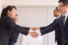 Povos asiáticos da equipe do negócio no terno formal que agita as mãos que terminam acima a reunião, foco seletivo, parceria feli fotos de stock royalty free