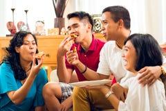 Povos asiáticos que comem a pizza no partido Fotografia de Stock
