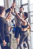 Povos atléticos novos no sportswear que dá a elevação cinco no gym foto de stock royalty free