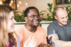Povos atrativos novos da reuni?o no caf? Os amigos conversam, t?m o divertimento, cocktail da bebida e comem-no imagem de stock royalty free