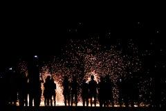 Povos borrados da silhueta do foco que olham a mostra da rotação do homem o fogo na praia foto de stock royalty free