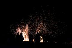Povos borrados da silhueta do foco que olham a mostra da rotação do homem o fogo na praia fotos de stock