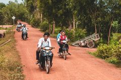 Povos cambojanos que conduzem 'trotinette's através de Camboja rural fotografia de stock royalty free