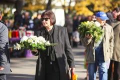 Povos com arranjos de flor no cemitério Imagens de Stock Royalty Free