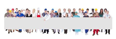 Povos com as várias ocupações que guardam o quadro de avisos vazio Imagem de Stock