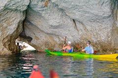 Povos com caiaque que exploram as cavernas, Melos, Grécia Imagem de Stock