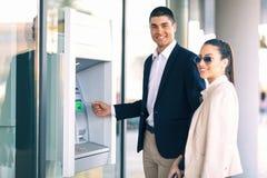 Povos com o cartão de crédito que está ao lado do ATM para retirar o dinheiro Foto de Stock Royalty Free
