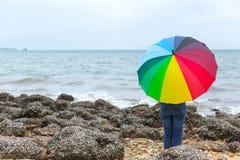 Povos com o guarda-chuva do arco-íris no litoral imagem de stock royalty free