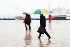 Povos com os guarda-chuvas no movimento foto de stock