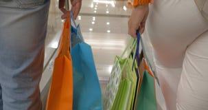 Povos com os sacos de compras que vão para baixo na escada rolante video estoque