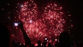 Povos com smartphones que olham fogos-de-artifício filme