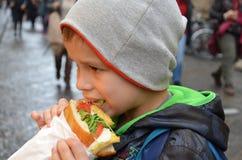 Povos, comida lixo, comer e estilo de vida - feche acima do homem novo, menino com sanduíche que come e que bebe na rua da cidade fotografia de stock