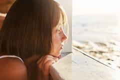 Povos, crianças, abrandamento, conceito da calma A criança adorável que inclina-se na plataforma de madeira, olhando o mar da AR  Imagens de Stock Royalty Free