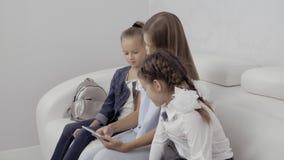 Povos, crianças, tecnologia, amigos e conceito da amizade - três meninas felizes com assento do computador do PC da tabuleta vídeos de arquivo