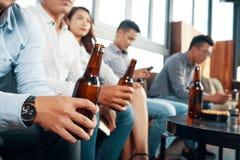 Povos da colheita com as garrafas de cerveja na barra fotos de stock royalty free