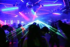 Povos da dança na frente dos raios laser de piscamento Imagens de Stock Royalty Free