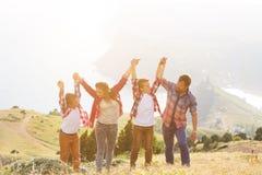 Povos da família de quatro pessoas que olham ao seascape bonito nas montanhas foto de stock royalty free
