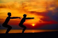 Povos da ioga que treinam e que meditam na pose do guerreiro fora pela praia no nascer do sol ou no por do sol Imagem de Stock Royalty Free