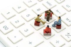 Povos da miniatura 4 que sentam-se nos grampos do vermelho colocados em uma calculadora branca reunião ou discussão como o concei fotografia de stock