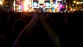 Povos da multidão que levantam as mãos e que apreciam no festival de música do concerto da música filme