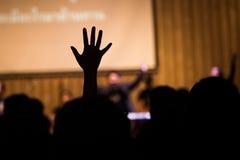 Povos da silhueta que levantam as mãos imagens de stock