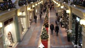 Povos da vista superior no shopping, borrado, escolhendo presentes para a precipitação do Natal e do ano novo filme