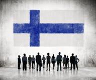 Povos das silhuetas que olham a bandeira finlandesa Imagem de Stock Royalty Free