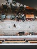 Povos de cima do assento em tabelas e do passeio rapidamente em uma alameda da cidade Fotografia de Stock Royalty Free