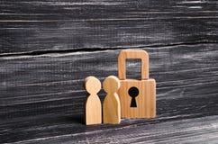 Povos de madeira com cadeado Dois povos com um fechamento Segurança e segurança, garantia, empréstimo para uma hipoteca confiscat fotografia de stock