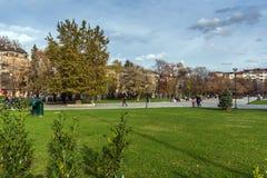 Povos de passeio no parque na frente do palácio nacional da cultura em Sófia, Bulgária Fotografia de Stock Royalty Free