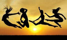 Povos de salto da felicidade da silhueta no por do sol imagens de stock royalty free
