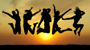 Povos de salto da felicidade da silhueta no por do sol Foto de Stock