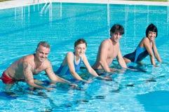 Povos de sorriso da aptidão que exercitam na piscina imagem de stock royalty free