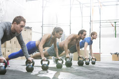 Povos dedicados que fazem flexões de braço com kettlebells no gym do crossfit Foto de Stock Royalty Free