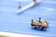 Povos diminutos: As famílias estão comemorando, comendo junto o ha fotografia de stock